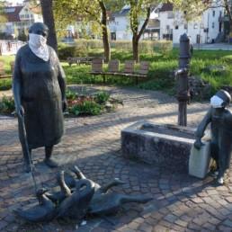 Skulpturen vor dem Rathaus mit Gesichtsmasken