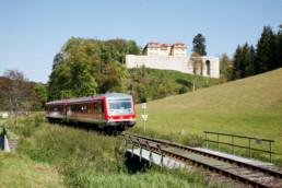 Bahnverkehr mit Gedenkstätte Grafeneck im Hintergrund