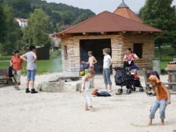 Familie mit spielenden Kindern an der Grillstelle am See