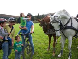 Kinder bestaunen zwei Kutschpferde